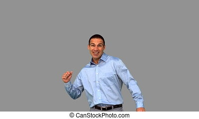 Cheerful businessman raising his fist on grey screen in slow...