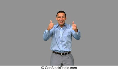 Cheerful businessman giving thumbs up on grey screen in slow...
