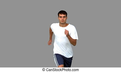 Handsome man jogging on grey screen in slow motion