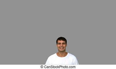 Cheerful man raising arms on grey screen in slow motion