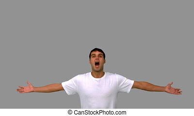 Handsome man jumping and raising arms on grey screen in slow...
