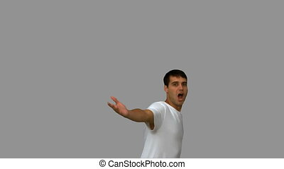 Handsome man turning and raising arms on grey screen in slow...