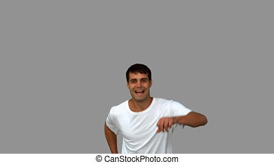 Handsome man giving thumbs up on grey screen in slow motion