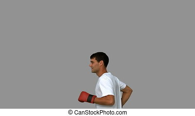 Man wearing boxing gloves on grey screen in slow motion