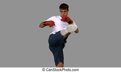 Boxer performing an air kick on grey screen in slow motion
