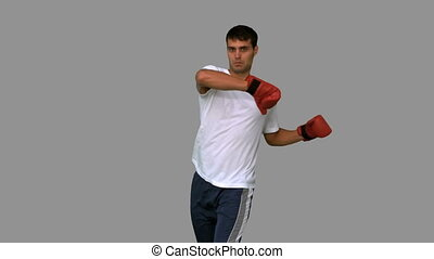 Boxer performing a high kick on grey screen in slow motion