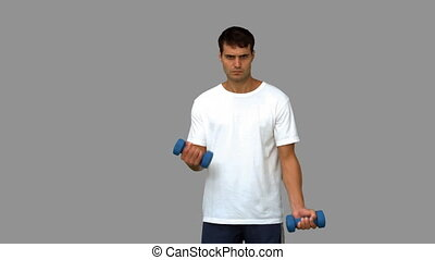 Handsome man lifting dumbbells on grey screen in slow motion