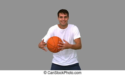 Man playing and dribbling with a basketball on grey screen...