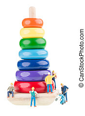 Miniature construction workers building a pyramid tower over white background