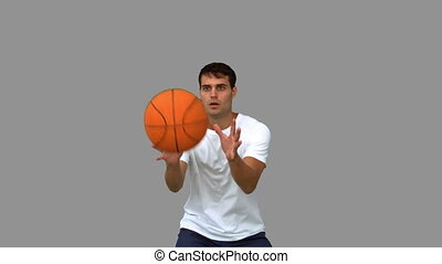 Man catching and throwing a basketball on grey screen in...