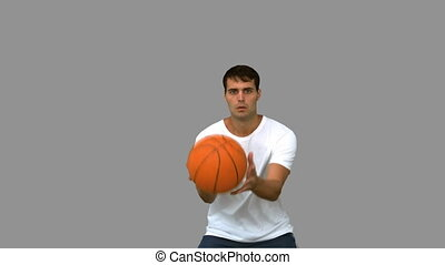Handsome man catching and throwing a basketball on grey...
