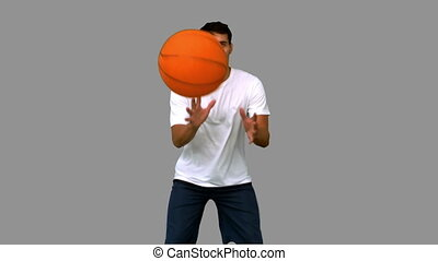 Handsome man playing with a basketball on grey screen in...