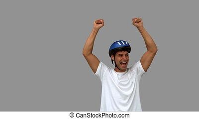 Man on his bicycle raising arms on grey screen in slow...