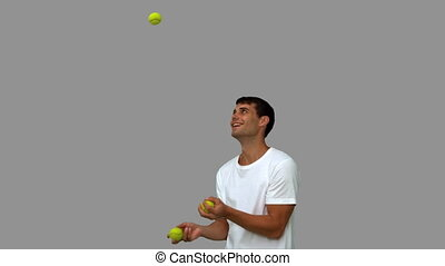 Man dribbling with balls on grey screen in slow motion