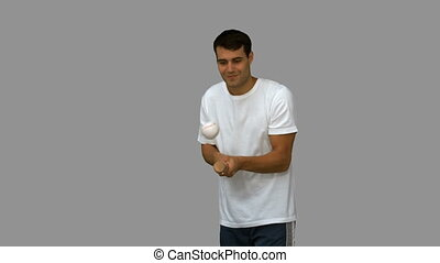 Man dribbling with a baseball on grey screen in slow motion