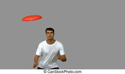 Man jumping and catching a frisbee on grey screen in slow...