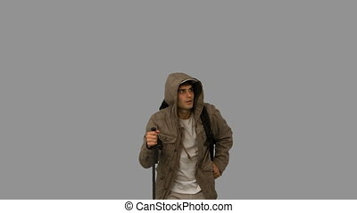 Man with a coat trekking on grey screen in slow motion