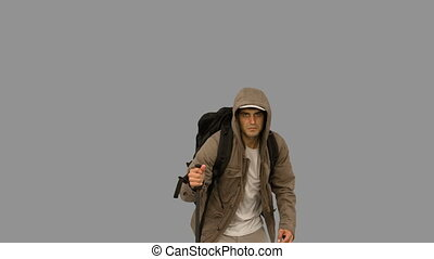 Man with a coat and a hiking stick running on grey screen in...