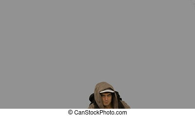 Man with a hiking stick jumping on grey screen in slow...