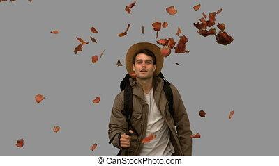 Man walking under leaves falling on grey screen in slow...