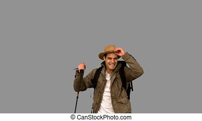 Cheerful man raising his hat on grey screen in slow motion