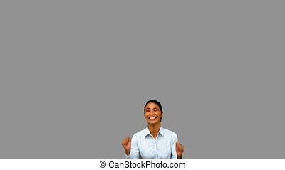 Cheerful businesswoman raising arms on grey screen