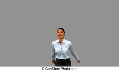 Happy businesswoman raising arms on grey screen in slow...