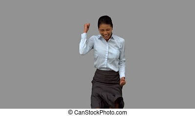 Cheerful businesswoman gesturing on grey screen in slow...