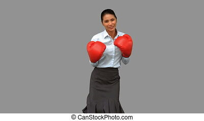 Businesswoman with boxing gloves hitting on grey screen in...
