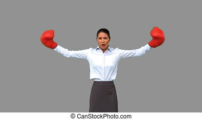 Businesswoman gesturing with boxing gloves on grey screen in...