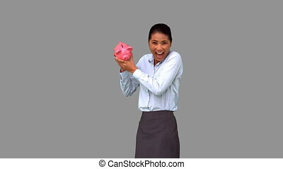 Businesswoman shaking a full piggybank