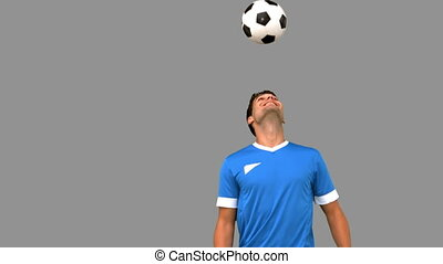 Man juggling a football with his head on grey screen in slow...