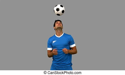 Man juggling a football with head on grey screen in slow...
