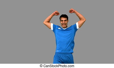 Happy football player raising arms on grey screen in slow...