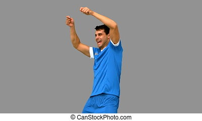 Happy football player gesturing after a goal