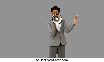 Businesswoman yelling into a megaphone on grey screen in...