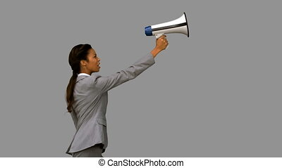 Businesswoman shouting into a megaphone on grey screen in...