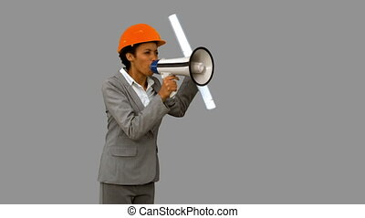 Angry architect using a megaphone on grey screen in slow...