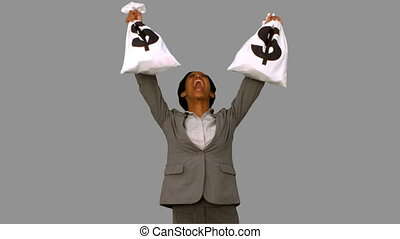 Businesswoman holding money bags on grey screen in slow...
