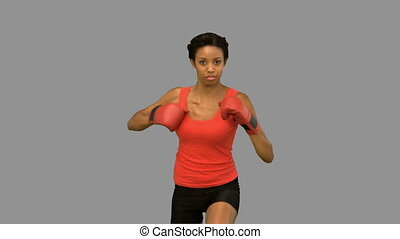 Woman boxing on grey screen in slow motion