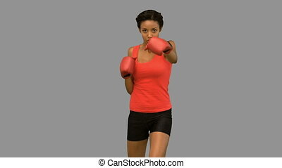 Attractive woman boxing on grey scr