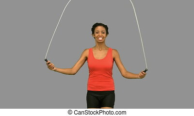 Woman working out with a rope on grey screen in slow motion