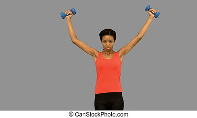 Woman lifting dumbbells on grey scr