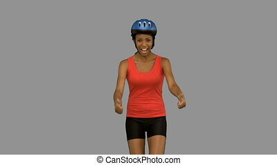 Cyclist woman giving thumbs up on grey screen in slow motion