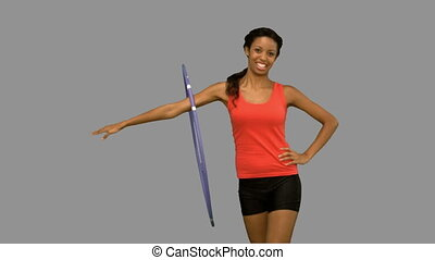 Woman working out with a hula hoop on grey screen in slow...