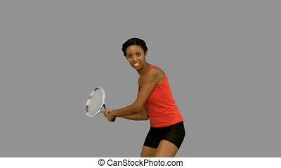 Pretty woman playing tennis on grey screen in slow motion