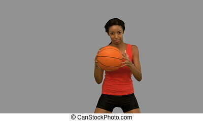 Pretty woman playing basketball on