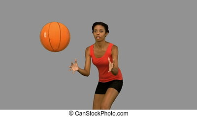 Woman catching and throwing a basketball on grey screen in...