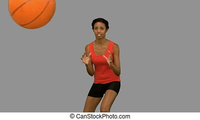Pretty woman catching and throwing a basketball on grey...