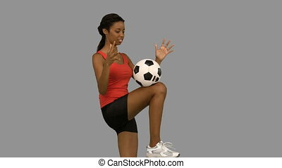 Woman juggling a football on grey screen in slow motion